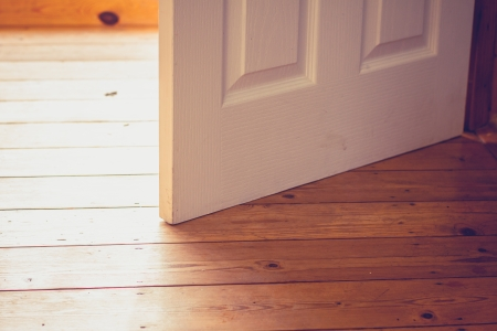open spaces: Open door and wood floor on a sunyy day Stock Photo