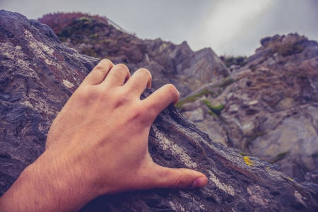 Close up on young man s hand as he is rock climbing  photo