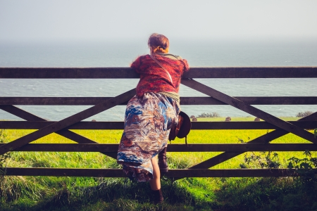 Young woman standing at gate and admiring sea and rural landscape photo