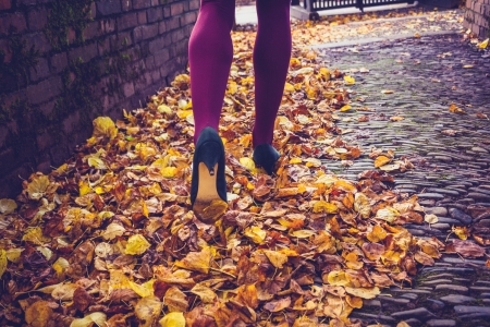 Young woman walking through leaves on autumn day