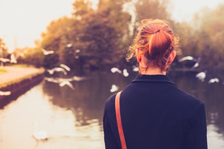 Rear view of young woman looking at birds by a lake