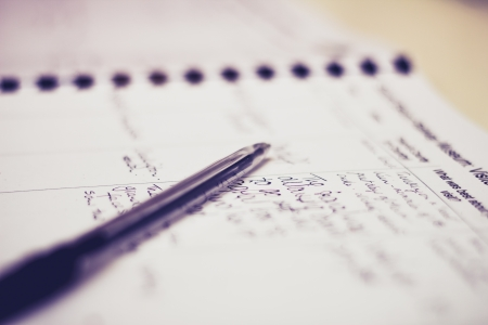 log book: Pen lying on a guestbook with handwriting Stock Photo