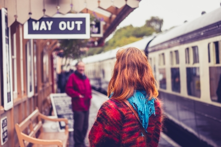 baggage train: Rear view of young woman at train station with steam train about to depart Stock Photo