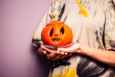 Young woman holding scary halloween pumpkin photo