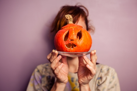 Young woman holding scary halloween pumpkin in front of her face photo