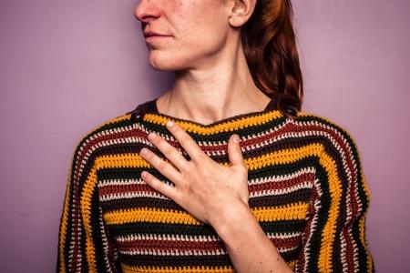 dolor de pecho: Mujer joven con su mano en el pecho Foto de archivo