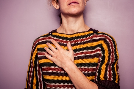 Young woman with her hand on her chest Stock Photo
