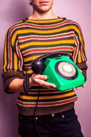 Young woman in colorful jumper holding an old telephone Stock Photo - 24124470