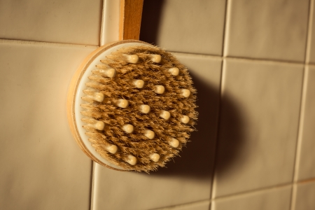 Brush against tiled wall in bathroom photo