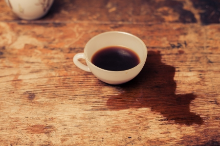 Cup of coffee on a wood table with spilled coffee