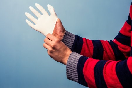 Man putting on a latex surgical glove photo