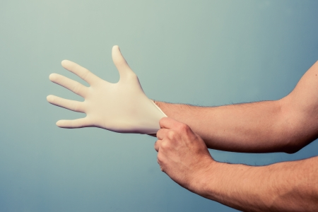 anti bacterial: Man putting on a latex surgical glove