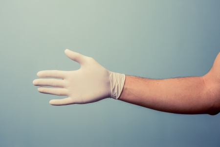 Hand wearing a latex surgical glove is extended for a handshake photo