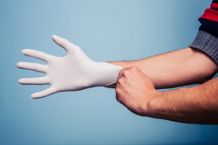 Young man is putting on a latex surgical glove photo
