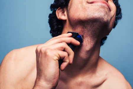 shaver: Young man is shaving with an electric shaver