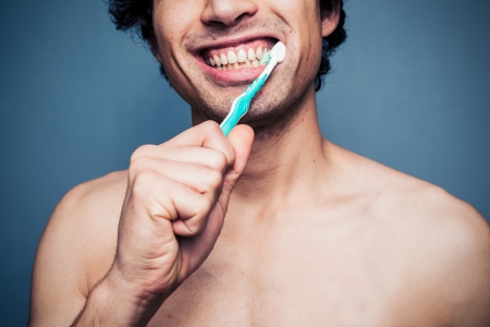 Happy young man is brushing his teeth