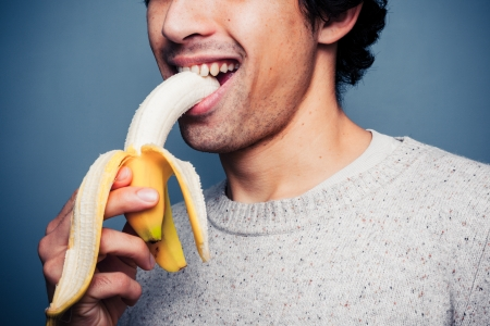 Young man is eating a banana photo