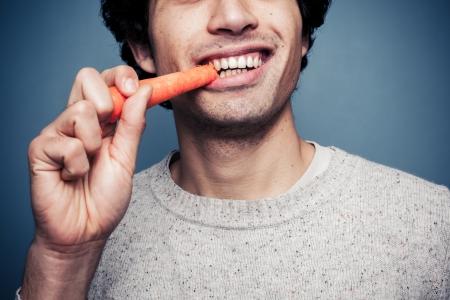 hombre comiendo: El hombre joven est� comiendo una zanahoria Foto de archivo