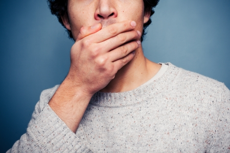 Young man is covering his mouth in shock