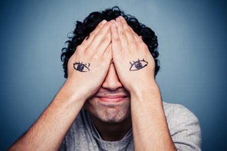 lenguaje corporal: Hombre con los ojos pintados en sus manos cubriendo su rostro Foto de archivo