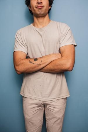 tattoed: Hombre tatuado joven de pie con los brazos cruzados Foto de archivo