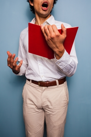 reciting: Young man singing or reciting from a red book Stock Photo