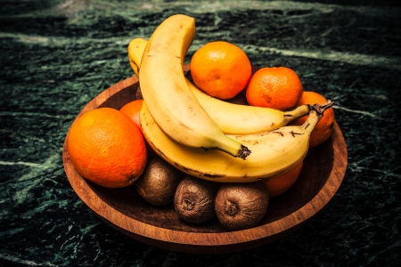 Bowl of fruit with bananas and kiwis photo