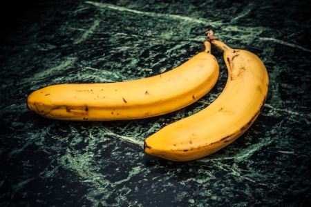 Two bananas on a marble surface photo