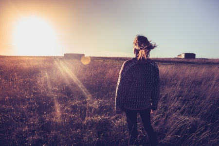 Young woman standing in a field at sunset Stock Photo