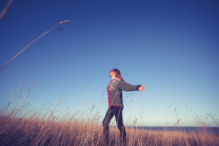 Young woman expressing joy and freedom in meadow at sunset photo