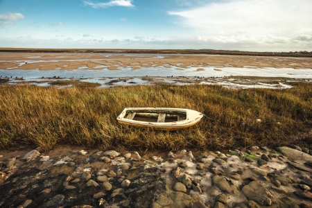 Abandoned rowing boat on the coast Stock Photo - 25097343