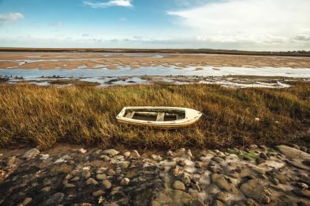 Abandoned rowing boat on the coast Stock Photo - 25097343
