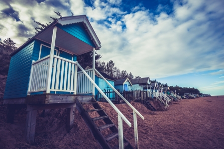 Colorful beach huts against a dramatic sky photo