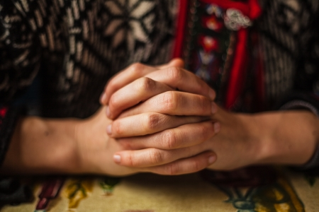 praying at church: The folded hands of a young woman Stock Photo
