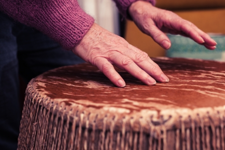 Old woman playing the bongo drums