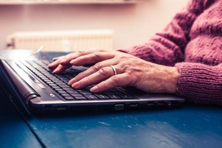Oude vrouw werkt op een laptop computer