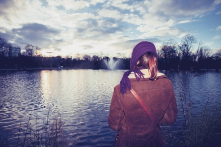 Young woman walking in park by pond at sunset photo