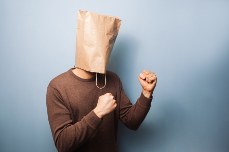 Man with bag over his head with his fists raised photo