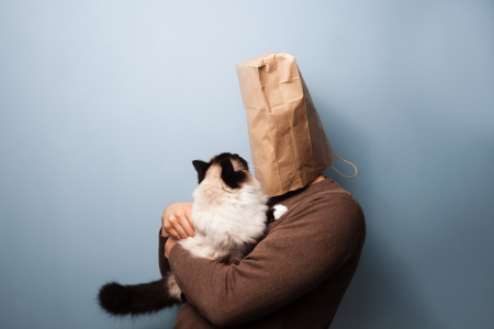 Man with bag over his head holding a cat photo