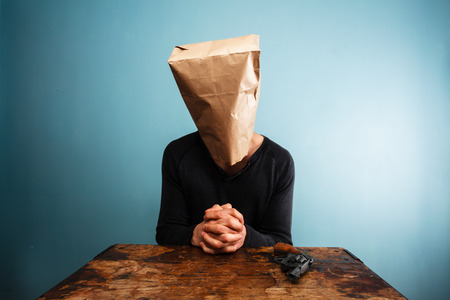 Praying man with a paper bag over his head at desk photo