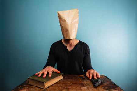 Man with bag over his head and hand on book and gun photo
