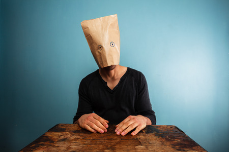 Stupid young man with a bag over his head at desk