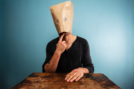 incognito: Stupid young man with a bag over his head at desk
