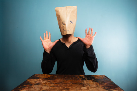 Startled young man with bag over his head at desk  photo