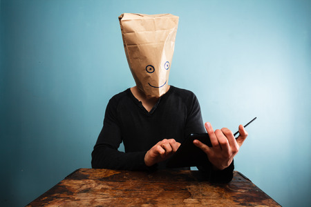 Man with bag over his head reading on a tablet photo