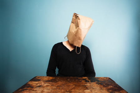 Sad man with a bag over his head sitting at a table photo