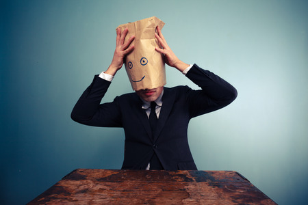 two faced: Businessman is placing a bag on his head