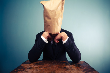 Businessman with bag over his head is upset photo