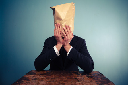 Businessman with bag over his head is upset