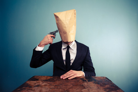 Businessman with bag over his head holding a gun to his head photo